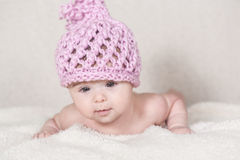 Beautiful newborn baby girl. With funny handmade pink hat, lying in her bed and smiling Stock Photography