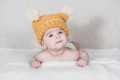 Beautiful newborn baby girl. With funny yellow hat, lying in her bed and smiling Royalty Free Stock Photos