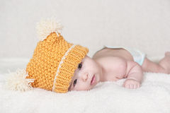 Beautiful newborn baby girl. With funny yellow hat, lying in her bed and smiling Royalty Free Stock Photo