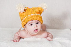 Beautiful newborn baby girl. With funny yellow hat, lying in her bed and smiling Royalty Free Stock Photography