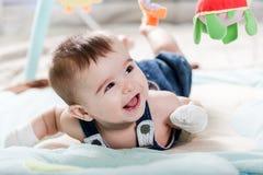 Beautiful newborn baby girl having fun. Beautiful newborn baby girl playing on the colorful rug Royalty Free Stock Photos