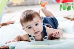 Beautiful newborn baby girl having fun. Beautiful newborn baby girl playing on the colorful rug Royalty Free Stock Photo
