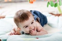Beautiful newborn baby girl having fun. Beautiful newborn baby girl playing on the colorful rug Stock Images