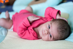Beautiful newborn baby girl. Lying in her bed and smiling Stock Images
