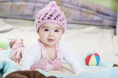 Beautiful newborn baby girl in pink hat. Beautiful newborn baby girl playing on the colorful rug Stock Photo