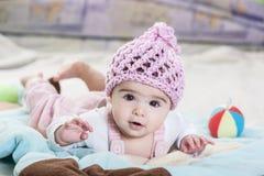 Beautiful newborn baby girl in pink hat. Beautiful newborn baby girl playing on the colorful rug Stock Photography