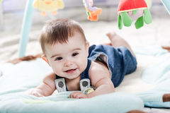 Beautiful newborn baby girl. Playing on the colorful rug Stock Images