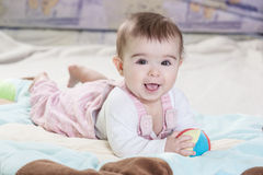 Beautiful newborn baby girl. Playing on the colorful rug Royalty Free Stock Image