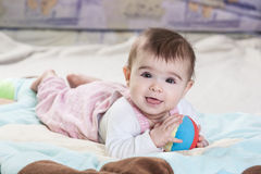 Beautiful newborn baby girl. Playing on the colorful rug Stock Photography