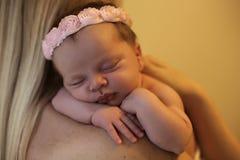Beautiful newborn baby girl sleeping on mom's shoulders. Studio photo of cute beautiful newborn baby girl sleeping on mom's shoulders Stock Photo