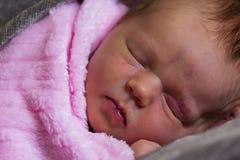 Beautiful newborn baby girl sleeping. Baby in pink blanket Stock Photography