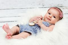 Beautiful newborn baby girl smiling. Beautiful and innocent newborn baby girl lying on the fur, looking towards camera, sweet face, studio portrait Royalty Free Stock Images