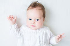 Beautiful newborn baby girl on a white blanket. Beautiful newborn baby girl in a white dress on a white blanket Stock Photos
