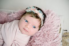 Beautiful newborn baby girl with wreath. Beautiful newborn girl with bright blue eyes in pink cloth and flowery wreath. Close-up portrait Royalty Free Stock Images