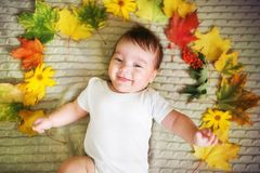 Beautiful newborn baby lies with maple leaves. Autumn concept Stock Images