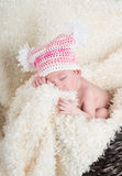 Beautiful newborn baby wearing a pink hat with white pom poms. Sleeping in a brown woven basket on a soft cream colored blanket Royalty Free Stock Photography