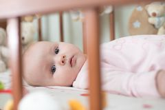 Beautiful newborn lies in crib. Beautiful newborn baby girl lies in crib Royalty Free Stock Photo