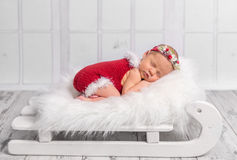 Beautiful newborn in red romper on sleigh cot. Beautiful newborn in red romper sleeping on sleigh cot with white fluffy blanket Royalty Free Stock Images