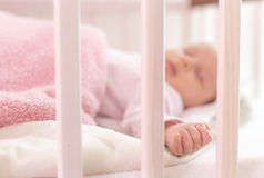A beautiful newborn sleep. In a crib sharpness on his hand Royalty Free Stock Photo