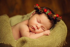 Beautiful newborn sleeping baby girl in wicker basket on a wooden background Stock Images