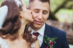 Beautiful newlywed bride and groom hugging in park. Face close-up Royalty Free Stock Photo