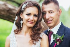 Beautiful newlywed bride and groom hugging in park. Face close-up Stock Photo