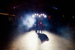 Blue light shine over wedding couple dancing in the darkness royalty free stock photo