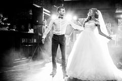 Beautiful newlywed couple first dance at wedding. Reception surrounded by smoke and lights b&w Royalty Free Stock Photography