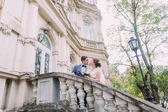 Beautiful newlywed couple in love posing on aged stairs at the old austrian palace Stock Photo