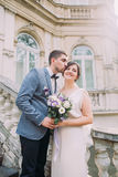 Beautiful newlywed couple in love posing on ancient stairs at the old austrian palace Royalty Free Stock Images
