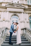Beautiful newlywed couple in love share kiss on ancient stairs at the old austrian palace Royalty Free Stock Photography