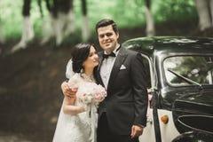 Beautiful newlywed couple posing near retro black car.  Stock Photography