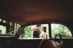Beautiful newlywed couple posing near retro black car.  Royalty Free Stock Images