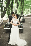 Beautiful newlywed couple posing near retro black car.  Stock Images