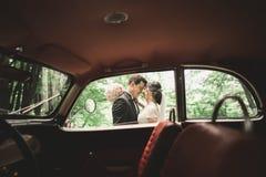 Beautiful newlywed couple posing near retro black car.  Stock Photo