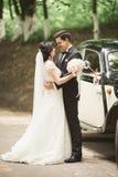 Beautiful newlywed couple posing near retro black car.  Royalty Free Stock Photography