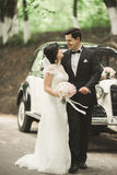 Beautiful newlywed couple posing near retro black car.  Royalty Free Stock Photos