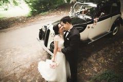Beautiful newlywed couple posing near retro black car.  Stock Image