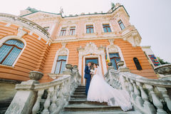 Beautiful newlywed couple on stairs in park. Romantic vintage palace at background Stock Photo