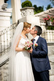 Beautiful newlyweds kissing at sunny day on street Stock Photography
