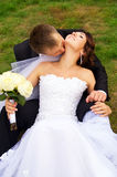 Beautiful newlyweds lay on the grass Royalty Free Stock Photography