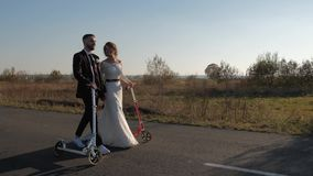 Beautiful newlyweds with a scooter in their hands are walking along the road of golden autumn stock video