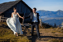 Beautiful newlyweds walking on the mountain countryside. Honeymoon.  Stock Photo