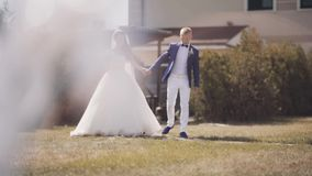 Beautiful newlyweds walking outside in nature. Groom kisses his bride, happy man and woman in wedding day. stock footage
