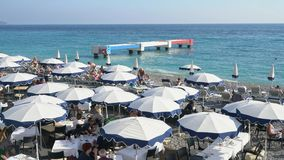The beautiful Nice beach with many visitor hiding in beach umbrellas stock video footage