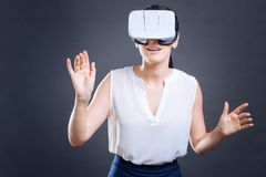 Beautiful nice businesswoman experiencing virtual reality. Power of technology. Beautiful pleasant nice businesswoman standing against black background and Stock Images