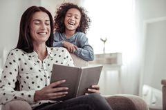 Beautiful nice mother reading a book together with a daughter stock photos