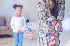Beautiful nice woman holding the US flag. American military service. Selective focus of a nice beautiful pleasant women holding a US flag behind her back and stock photo
