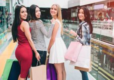 Beautiful and nice young ladies are posing. They are looking back on camera and smiling. Girls are happy because they. Are shopping royalty free stock images