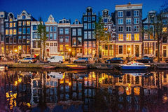 Beautiful night in Amsterdam, illumination of buildings and boat Stock Images